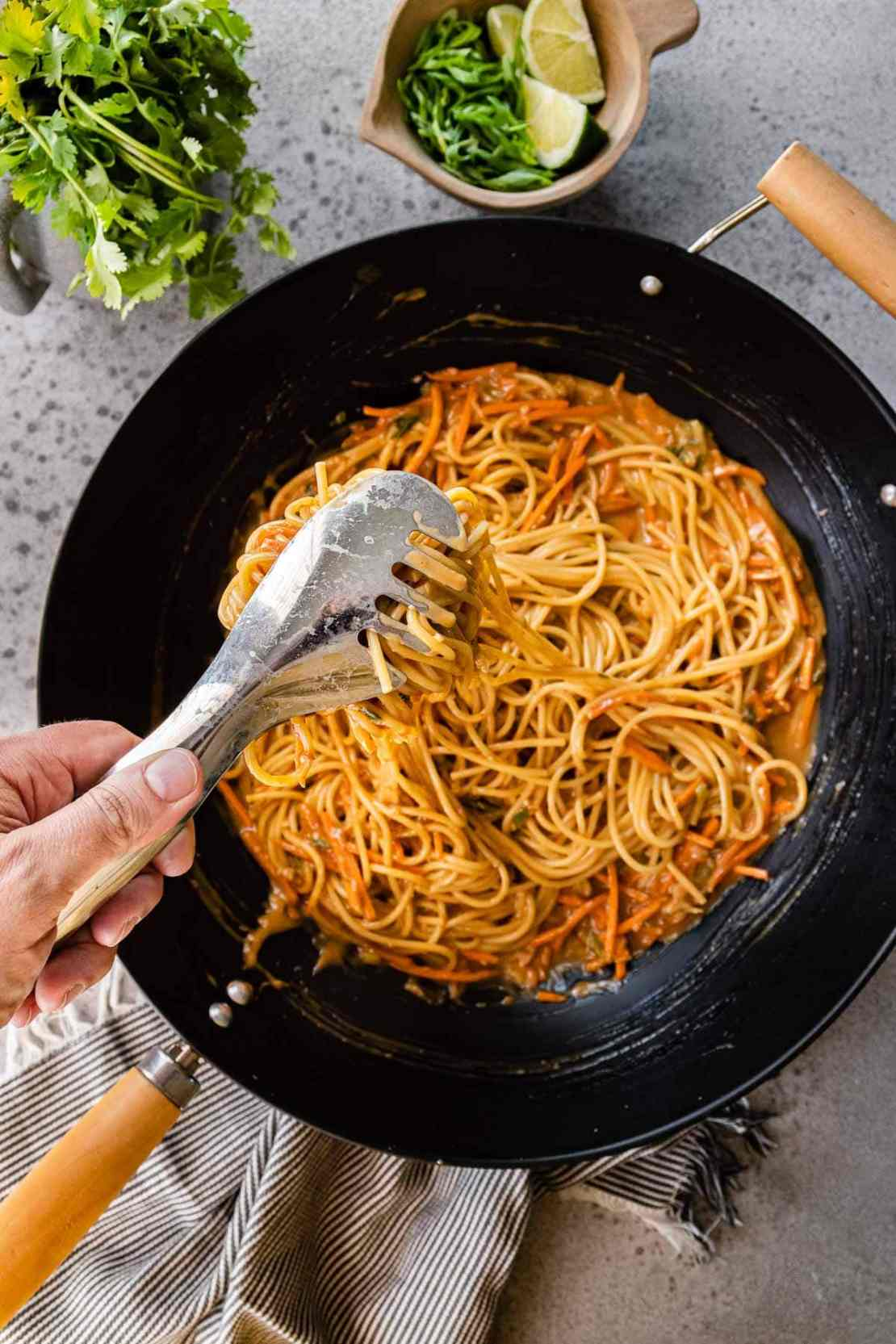 Mixing noodles and sauce in pan for Spicy Peanut Noodles