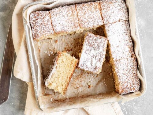 Butter Cake dusted with powdered sugar sliced in baking pan