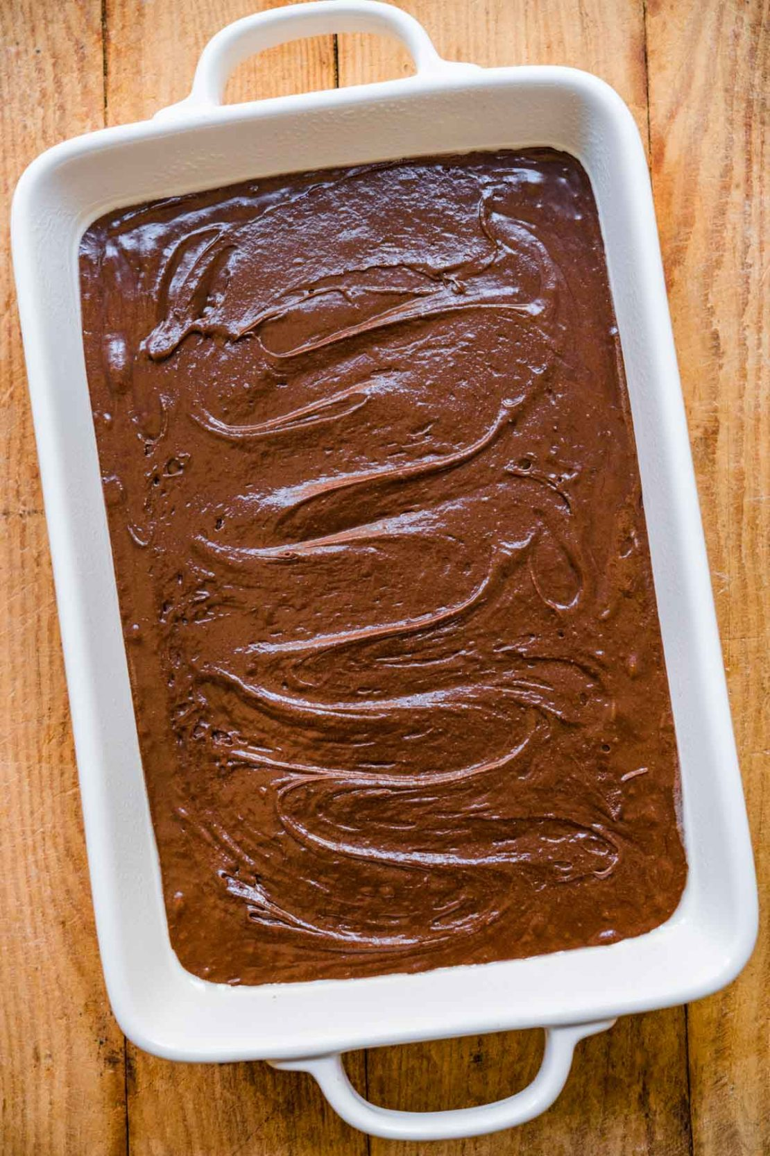 Brownie batter in baking dish for Crispy Chocolate Peanut Butter Brownie Bars