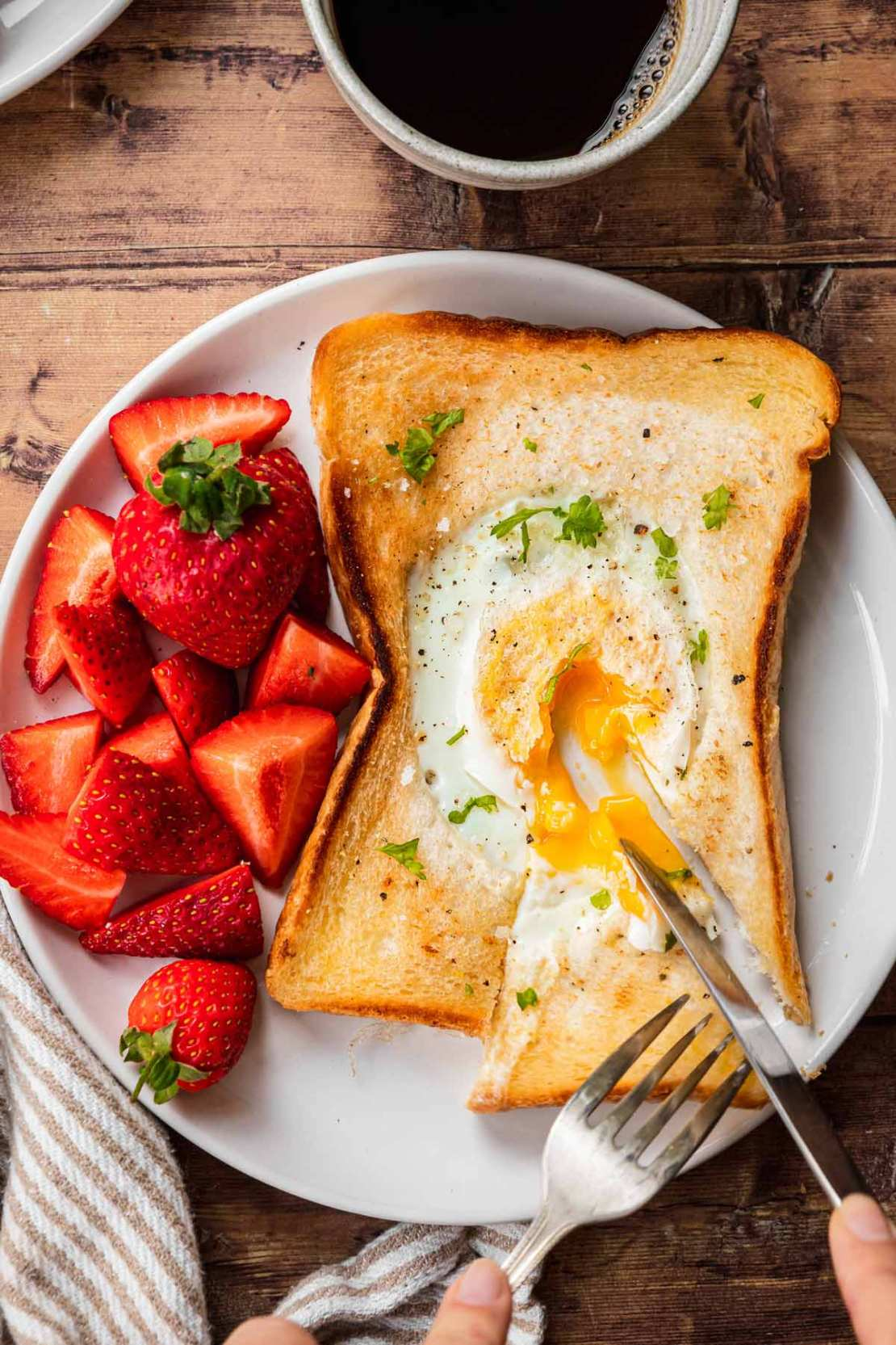Egg in a Hole sliced open with runny egg on plate