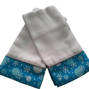 duas fraldinhas de ombro dobradas sobrepostas com barrado azul estampado com flocos de neve