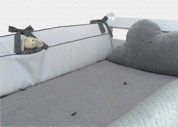 close de kit de berço branco e cinza composto por: lateral com coelhinho no bolso, almofada de nuvem e rolo lateral