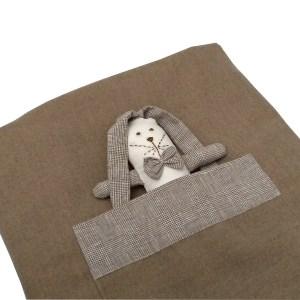 close de manta de lã bege dobrada com bolso e mini naninha orelhuda