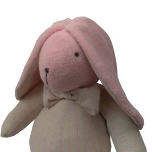 coelho de pano rosa e bege com laço no pescoço