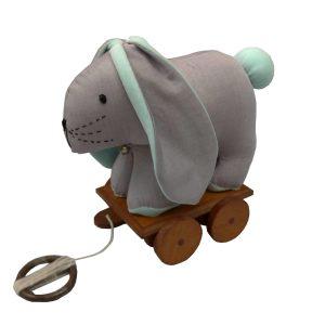 brinquedo infantil coelho de pano cinza e verde menta sobre base em madeira com rodinhas para criança puxar.