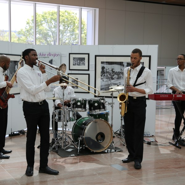 Students perform in the pavilion in front of an exhibit