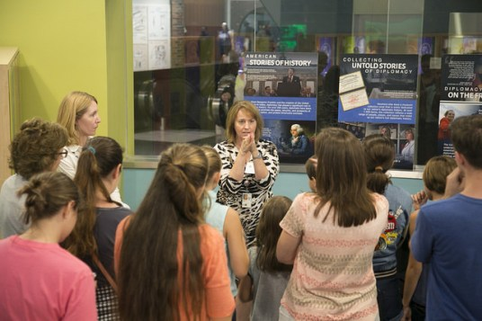 Alison Mann speaks to a group at the Diplomacy Center exhibit testing
