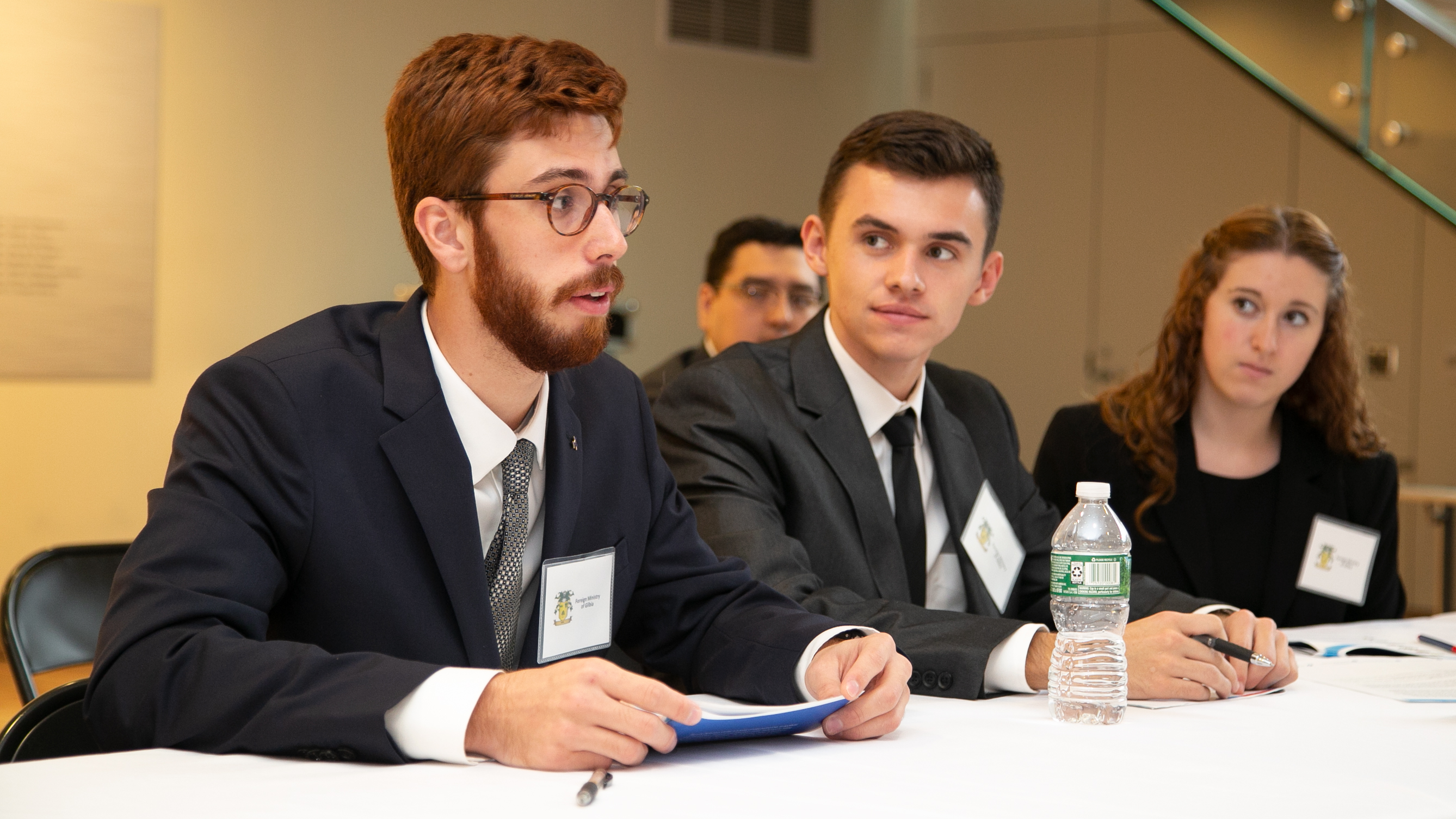 One of three students speak at a table at a simulation.