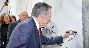 George H.W. Bush signs a piece of the Berlin Wall