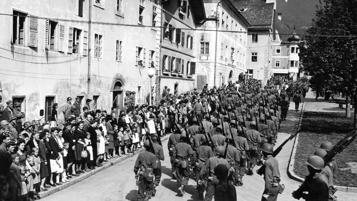 Crowd of soldiers walk by citizens in a black and white photo with Austrian Alps in background
