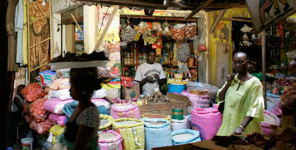 Vendor Ousmane Cisse, center right, waits for customers in a market on the outskirts of Dakar, Senegal. Cisse says he has had to increase the price of a kilo of rice, a staple of the Senegalese diet, by 30 percent since last year.