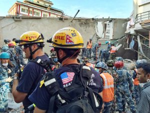 In this May 12, 2015 photo provided by the U.S. Agency for International Development, Los Angeles County Fire Department urban search and rescue team memebres work to recover survivors from a four-story building that collapsed in the earthquake in Singati, a mountain village in Nepal. The temblor was an aftershock to the April 25 main Gorkha earthquake that killed more than 8,000 people. The Disaster Assistance Response Team included 57 urban search and rescuers each from Los Angeles County and Fairfax County, Va. (Kashish Das/USAID/via AP)