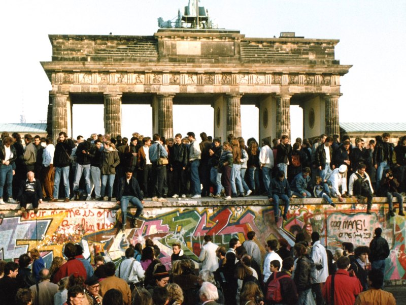 People lined the top of the Wall in 1989 with the Brandenburg Gate in the background as a crowd gathered below