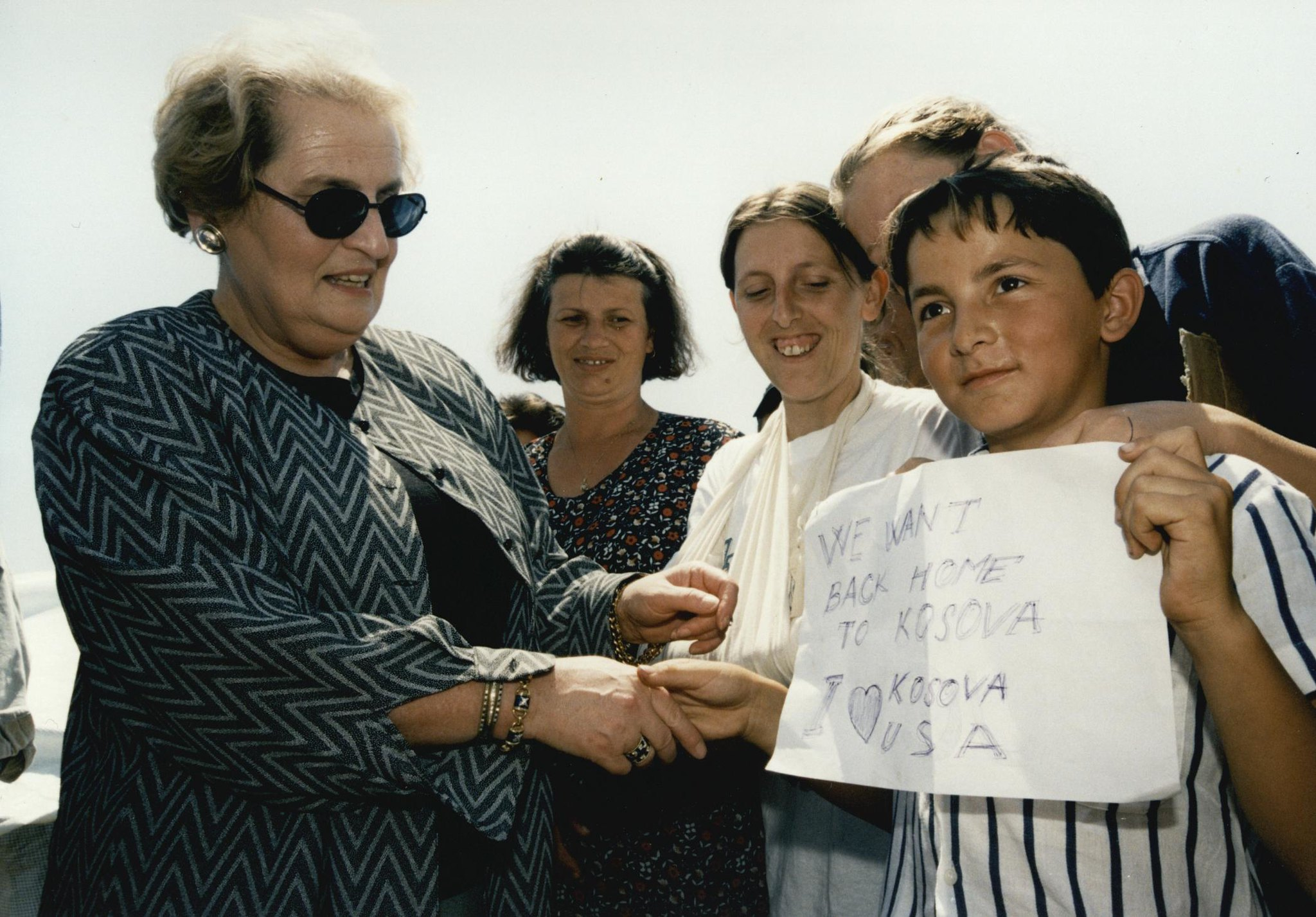 "U.S. Secretary of State Madeleine Albright greets boy holding sign that reads: ""We want back home to Kosova."""