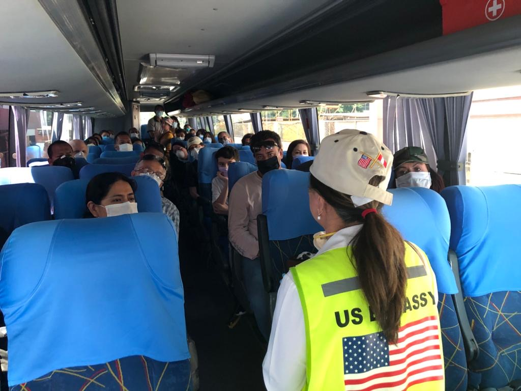 American passengers receive instructions from U.S. Embassy staff as they travel to the airport for their repatriation flights from Lima, Peru.