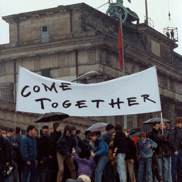 East Berliners stand on Berlin Wall