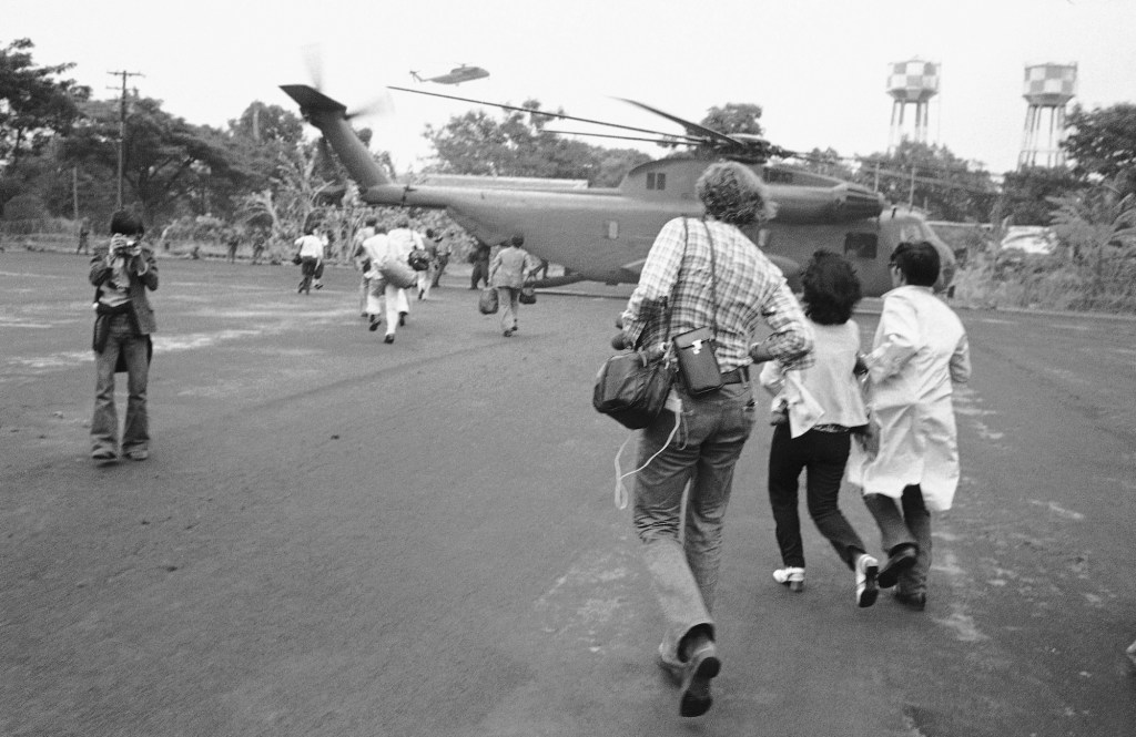 American and Vietnamese refugees running toward helicopter during Fall of Saigon