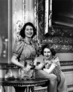 Princesses Elizabeth and Margaret Rose pose with a beloved corgi