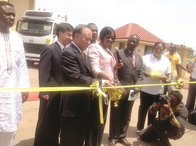 Mrs Dzifa Attivor (2nd left) being supported by Mr Gao Wenzhi to cut the tape for the launch of the A7 Sinotruk trucks.