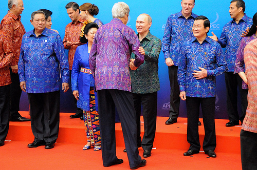 U.S. Secretary of State John Kerry, dressed in a traditional batik shirt, speaks with Russian President Vladimir Putin before the two join other heads of delegation for a family photo before the APEC Leaders Dinner on October 7, 2013. in Bali, Indonesia. [State Department photo / Public Domain]