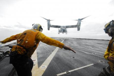 The first ever landing (touch and go) of a V-22 Osprey aboard the USS Ashland (LSD-48), underway in the Leyte Gulf, Philippines. Boatswain's Mate Third Class Brian Sherlock, of Tucson, Arizona, directs the first-ever landing of this type aircraft aboard. BM3 Sherlock is the Landing Signalman Enlisted member chosen to direct this operation. (Courtesy Photo by Navy Media Content Services)