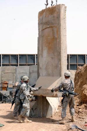 U.S. Soldiers of Headquarters and Headquarters Company, Brigade Special Troops Battalion, 3rd Brigade Combat Team, 82nd Airborne Division, guide a concrete barrier into a new position at Joint Security Station Loyalty, eastern Baghdad, Iraq, on May 17, 2009