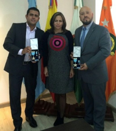 Colonel Juliette Kure Parra, head of Interpol Colombia, presents U.S. Embassy Bogota ARSO-I Antonio and CFI Eduardo with the prestigious Major Juan Carlos Guerrero Barrera Medal, June 22, 2015. (U.S. Department of State photo)