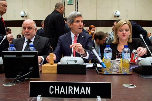 U.S. Secretary of State John Kerry, flanked by Iraqi Prime Minister Haider al-Abadi and State Department Executive Assistant Jennifer Davis, bangs the gavel to begin a meeting of more than 60 anti-ISIL coalition parties held on December 3, 2014, at NATO Headquarters in Brussels, Belgium. [State Department photo /Public Domain]