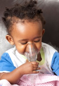 Photo of a young girl using an asthma inhaler. Image used courtesy of NICHD.