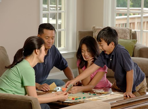 An Asian family (adult male and female and two adolescents, male and female) sitting around a coffee table playing a board game