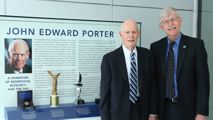 Dr. Francis Collins poses with John Edward Porter in front of a wall display honoring Mr. Porter