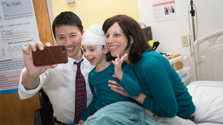 Photo of Dr. Yu taking a selfie with Mila and her mom