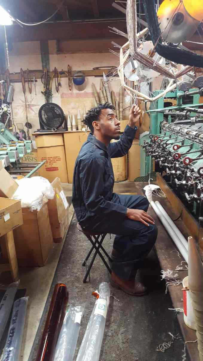 """Jamar """"Soup"""" Campbell examines the factory threading machines that will be a part of the dance climax."""