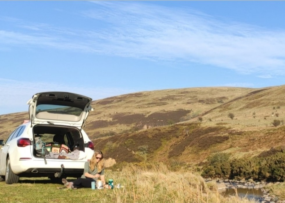 Zoe sits in front of her white car with an open boot cooking tea in front of rolling hills.