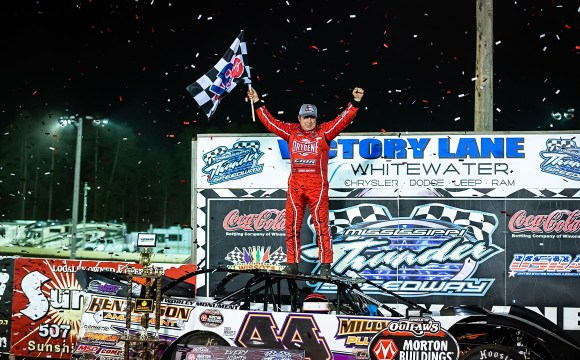Madden stands on his car and celebrates in victory lane.
