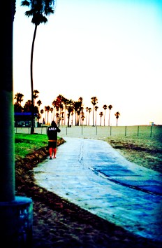 a man with a sweatshirt with East written on the back strolling the bike path at Venice Beach