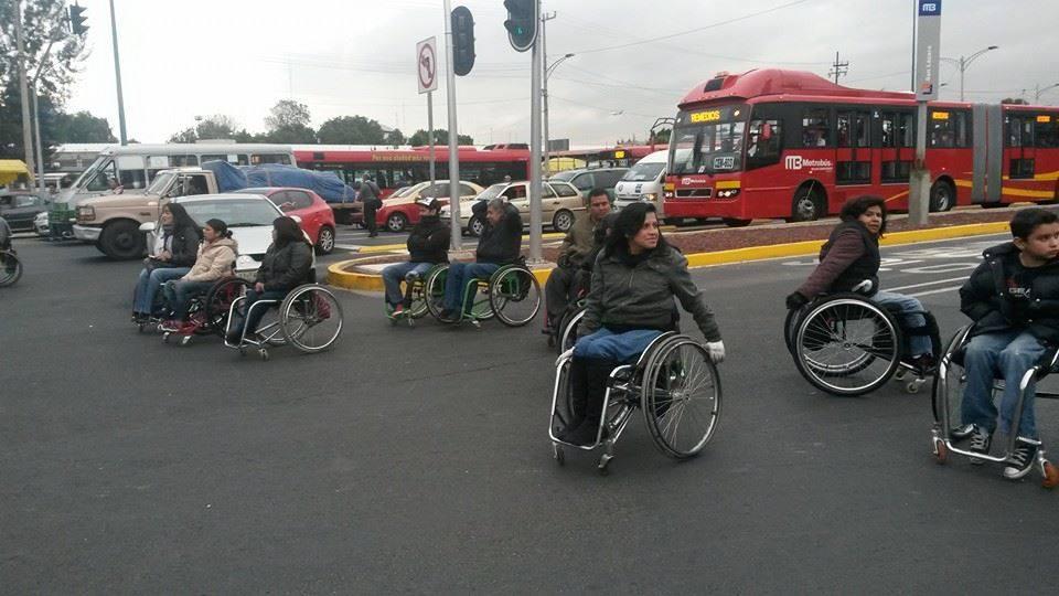 muejeres y hombres en silla de ruedas parando el tránsito en una avenida de la ciudad de México