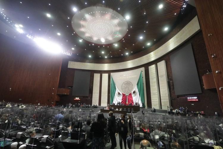 Panorámica del salón principal de la Cámara de Diputados. Al frente se ve la tribuna y el muro adornado con dos grandes banderas de México unidas al centro, debajo del escudo nacional. Foto: Comunicación Social de la Cámara de Diputados.