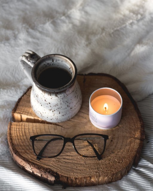 A mug of coffee, a lit candle, and a pair of eyeglasses sit on a round piece of wood on a bed with blankets in the background.
