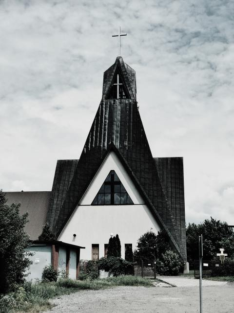 a white church stands against a grey sky.