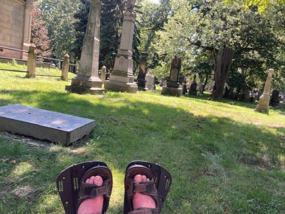 Dion's feet, on his wheelchair foot rests, are visible in the foreground of the photo.  In the backgroung are tombstones and trees.