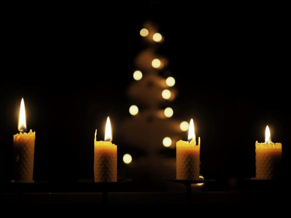 four lit advent candles stand in a dark room.  A Christmas tree is in the background.