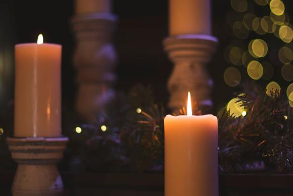 Two lit candles can be seen in front of greenery, and two more candles in the background.