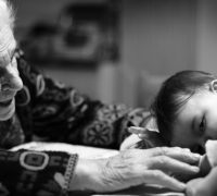 a black and white photo shows an elderly grandmother reaching out to a baby granddaughter who is laying her head down. The two are touching and both look happy.