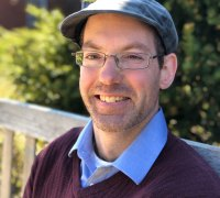 Mike is a white man with glasses. He is wearing a flat peaked cap, and a sweater over a collared shirt. he is sitting outside in the sun and is smiling at the camera.