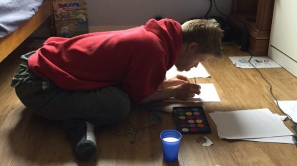 A younger man with Down syndrome leans over on the floor of his bedroom as he paints a picture  on a sheet of paper