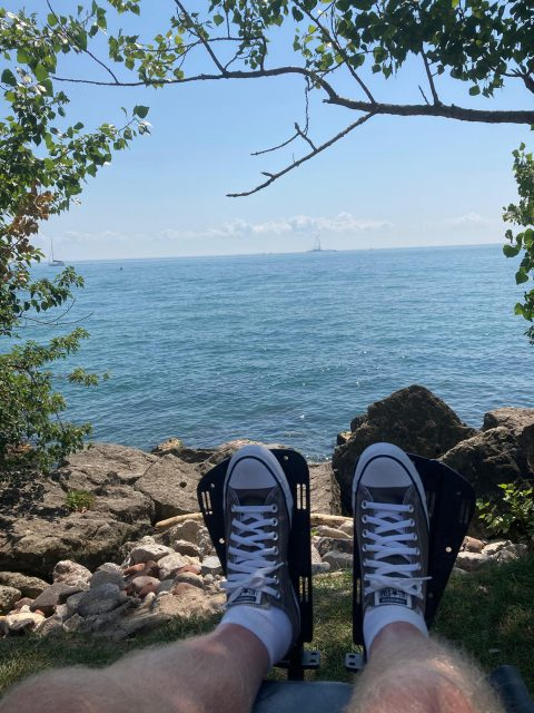 Dion's feet, wearing converse sneakers, are visible in the foreground, resting on his wheelchair foot rests.  in the background is a rocky shore and then a wide expanse of lake.