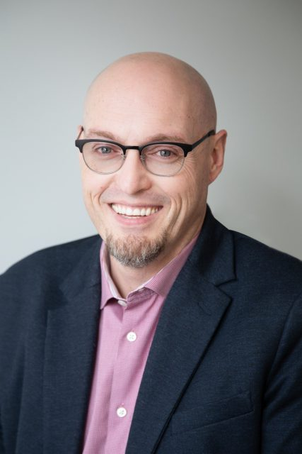 Dwayne is a white man who is bald and has a goatee. He wears a dark suit, and glasses and he is smiling at the camera.
