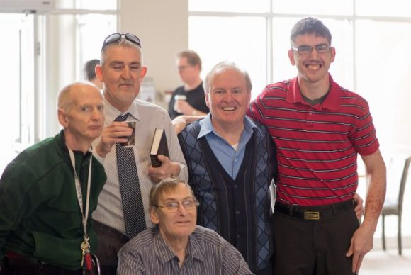 A group of white men, of varying ages, with and without visible disabilities stand together in a church lobby. Most are smiling at the camera and some have their arms around each other.