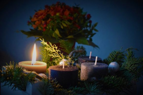 One candle is list beside three unlit candles.  There is greenery around the candles and a bouquet of flowers in the background.
